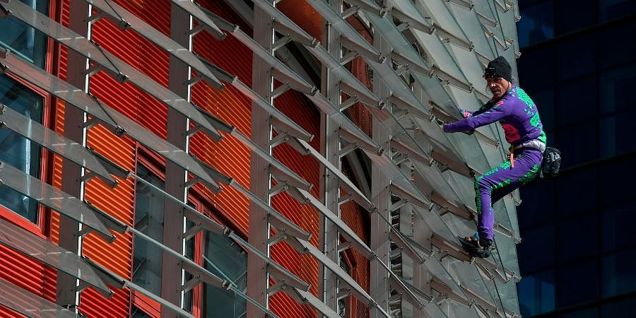 French skyscraper climber Alain Robert, known as the French Spiderman, climbs the Agbar Tower in Barcelona on March 4, 2020 as a symbolic action to call on governments and individuals across the world to be more responsible in the face of the COVID-19 coronavirus outbreak.