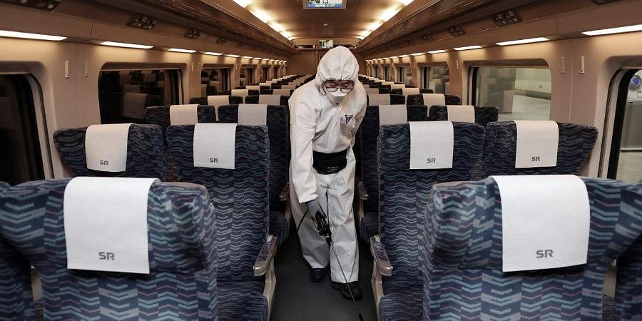 A worker wearing protective gears sprays disinfectant as a precaution on a train against the new coronavirus at Suseo Railway Station in Seoul, South Korea, Tuesday, Feb. 25, 2020.
