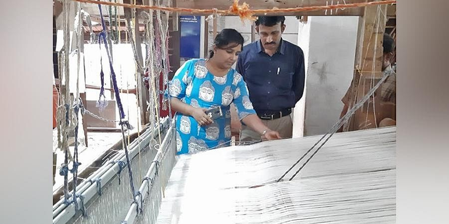 Sangeetha and her husband Abhayan checking out the weave at a loom