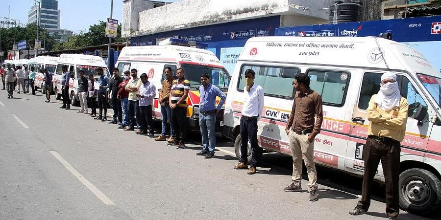 Staff of ambulance service stand in front of Lohiya Hospital after discontinuing their services to protest not being given any preventive material by the government amid coronavirus pandemic, in Lucknow