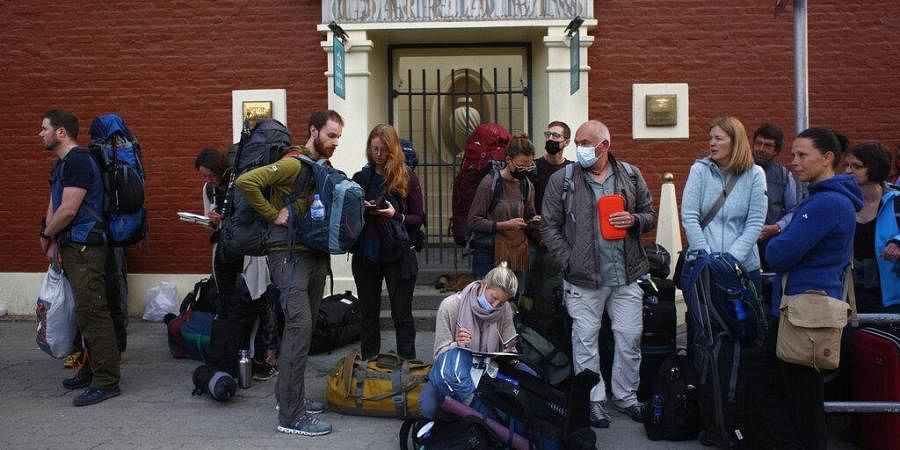 Stranded German tourists wait for a bus to take them to the airport in Kathmandu, Nepal, Friday, March 27, 2020.
