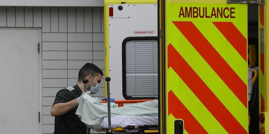 A patients is helped from an ambulance as they arrive at St Thomas' Hospital in London.