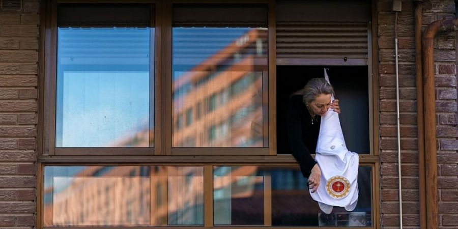 A woman places a penitent hood of the 'San Cosme and San Damian' brotherhood in the window in Burgos on April 8, 2020, as Holy Week processions were canceled during a national lockdown to prevent the spread of the COVID-19 disease. In the week leading up to Easter Sunday, hundreds of colourful processions featuring penitents in cone-shaped hoods and centuries-old religious floats traditionally flood the streets of villages and cities across Spain. But with a nationwide lockdown in place to curb the spread of the coronavirus, Spaniards this year are finding ways to mark Holy Week from their homes, by blasting religious music from their balconies or viewing videos of last year's parades.