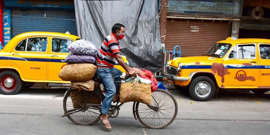 A cycle puller carries boxes of sack vegetables on his cycle while passing through an empty road during lockdown awake of a novel coronavirus in Kolkata