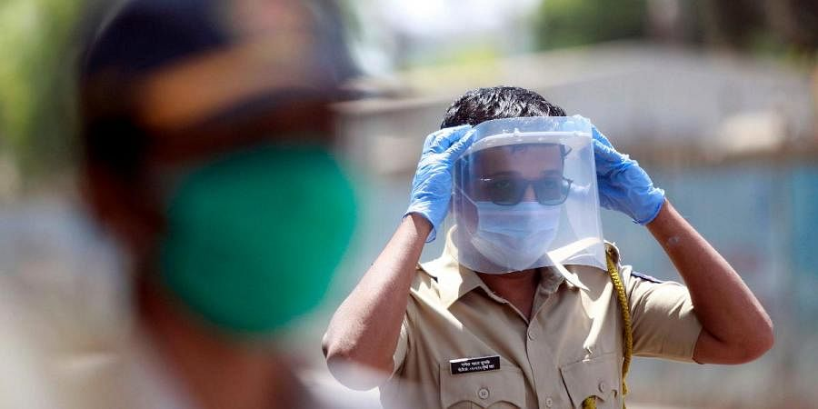 A police personnel wears plastic sheet on face while on duty during the nationwide lockdown in Mumbai