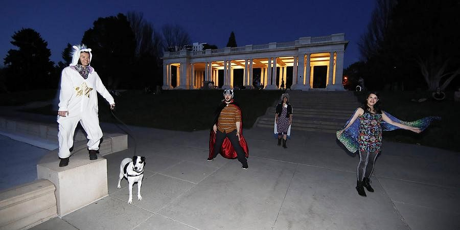 Irina Bocomolova and her dog, Darby, join Brice Maiurro, Shelsea Ochoa and Anna Beazer, from left, in a group howl in Cheesman Park in Denver. American howling