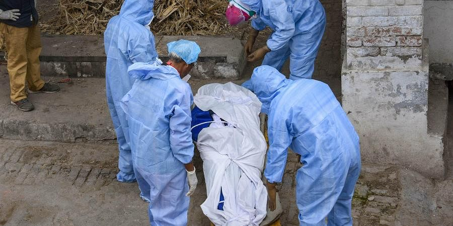 Medics prepare to cremate a COVID-19 patient during the nationwide lockdown to curb the spread of coronavirus. (Photo | PTI)