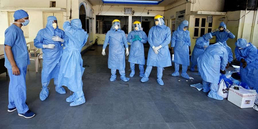 Doctors wearing protective suits before they start collecting swab from people, who are under home quarantine to test for COVID-19