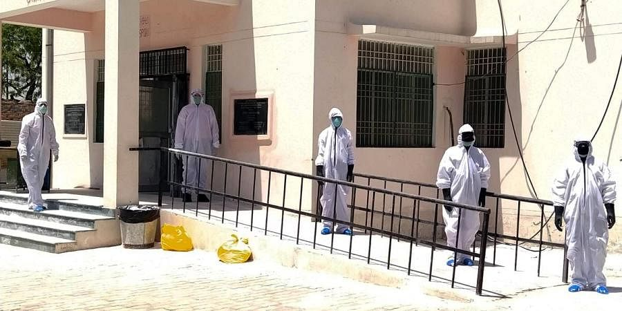Medical staff wear protective gear as they arrive at a hospital where COVID-19 positive patients are being treated in Prayagraj