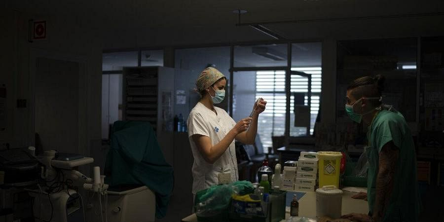A healthcare worker prepares medication for a COVID-19 patient at one of the intensive care units.