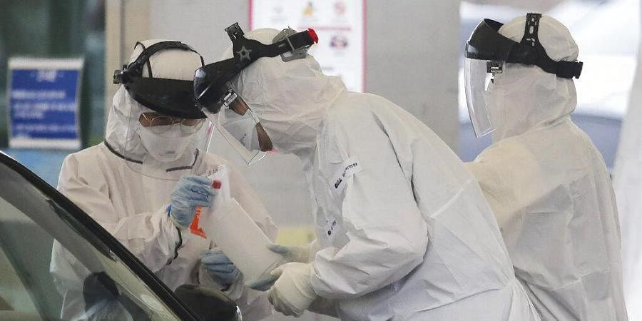 In this March 1, 2020 file photo, medical staff wearing protective suits take samples from a person with suspected symptoms of the new coronavirus at a drive-thru virus test facility in Goyang, South Korea.