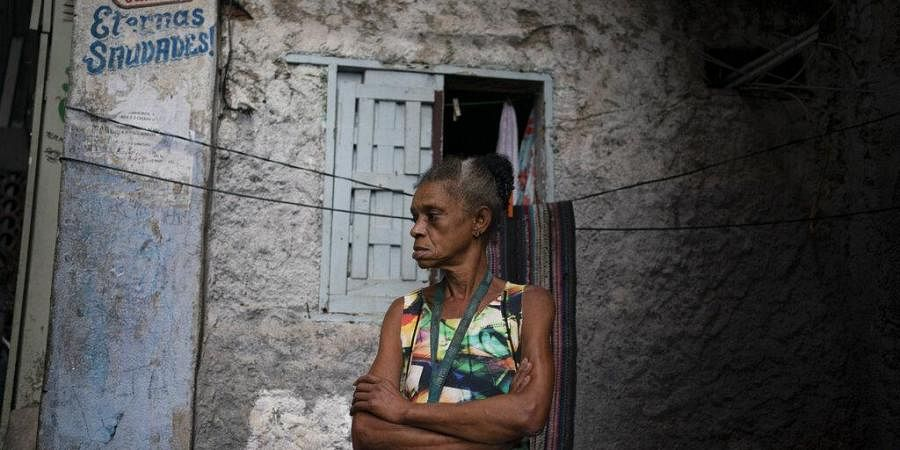 A woman stands in an alleyway as she watches the brothers Thiago Firmino and Jorge Alexandre, spraying disinfectant to help contain the spread of the new coronavirus, at Santa Marta slum in Rio de Janeiro, Brazil, Friday, April 10, 2020.