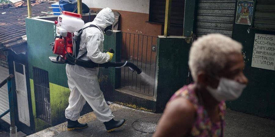 Thiago Firmino sprays disinfectant on an alley to avoid the spread the new corona virus at Santa Marta slum in Rio de Janeiro, Brazil, Friday, April 10, 2020.
