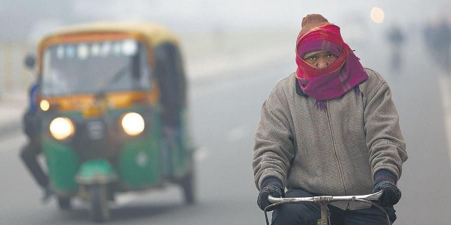 A man rides a bicycle on a road blanketed by dense fog in New Delhi on Saturday.