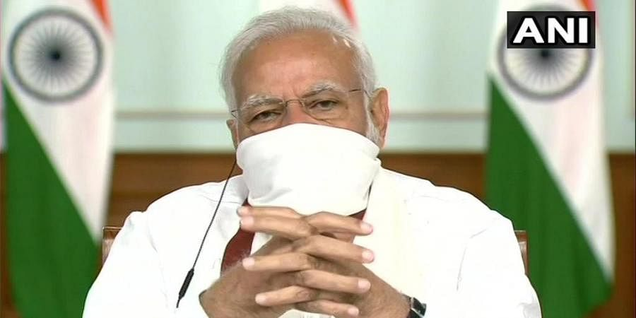Prime Minister Narendra Modi seen wearing a mask during video-conferencing with the Chief Ministers. (Photo | ANI)