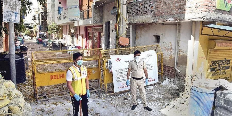 Police personnel stand guard at Gali No. 6, Sangam Vihar, an area which has been identified as a containment zone on Sunday.