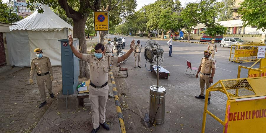 A police officer sanitises himself in front of a fan with a sprayer installed by Barakhamba Road Police Station amid a nationwide lockdown in the wake of coronavirus pandemic near Bengali market area in New Delhi