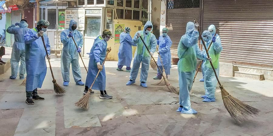 South Delhi Municipal Corporation workers wearing protective suits clean the Nizamuddin residential area in wake of the coronavirus pandemic during the nationwide lockdown in New Delhi