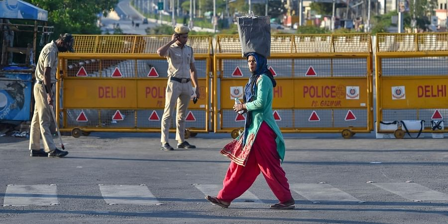 A migrant walks past police barricades placed near Ghazipur during a nationwide lockdown