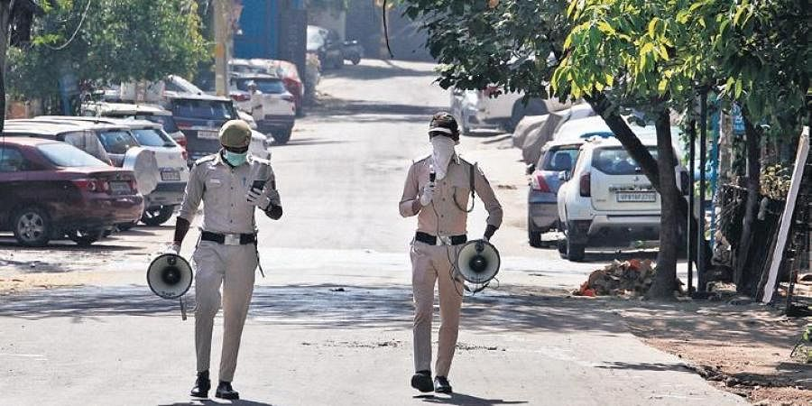 Police personnel make public awareness announcements about coronavirus in New Delhi during the nationwide lockdown on Monday