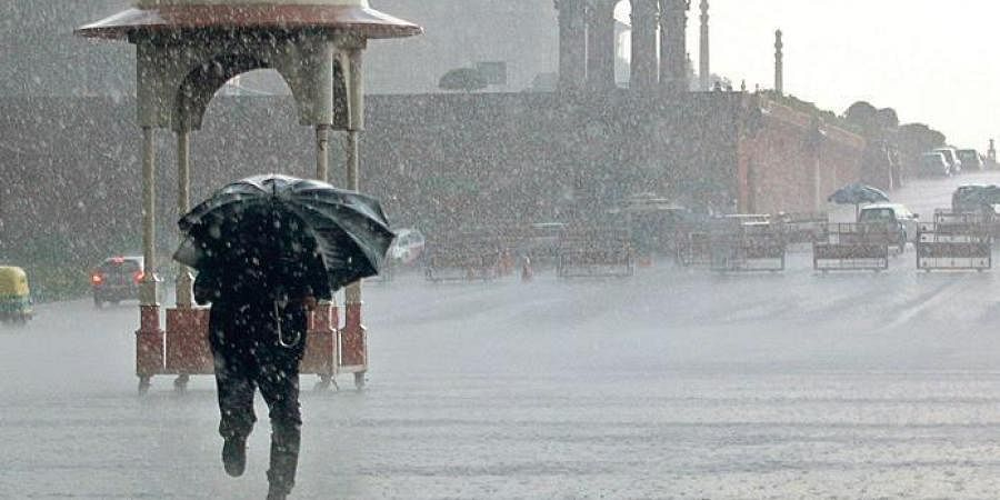 A man shields himself as heavy rains accompanied by hailstorm lashed parts of the national capital, near Vijay Chowk in New Delhi.