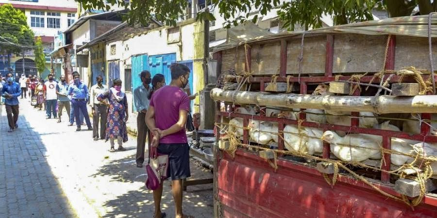Locals maintain social distance as they stand in a queue to buy chicken during the nationwide lockdown to contain the spread of the coronavirus in Guwahati