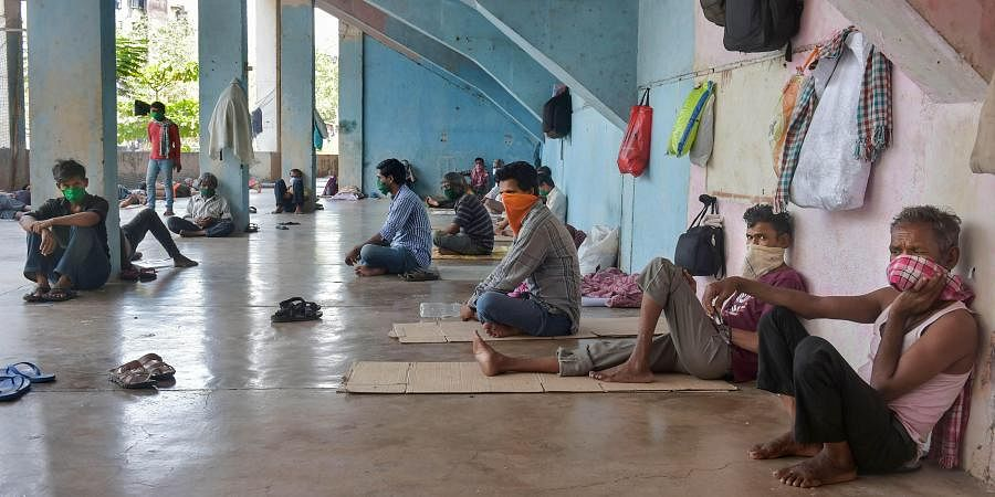 Migrant workers and homeless people rest at a temporary camp set up on the premises of a stadium, during ongoing COVID-19 lockdown in Thane