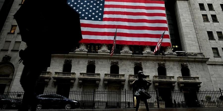 A woman walks past the New York Stock Exchange. (Photo| AFP)