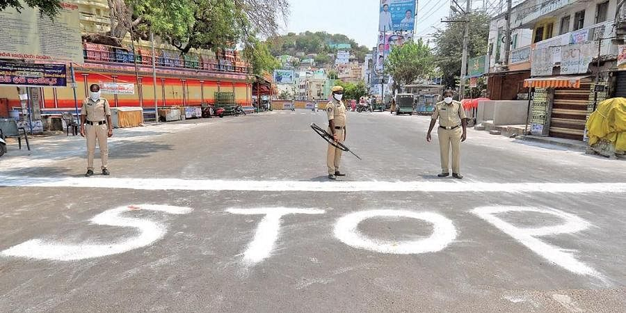 Sanitation workers wrote 'Stop' on the road to restrict people from entering a contaminated zone at Machacaram in Vijayawada on Wednesday.