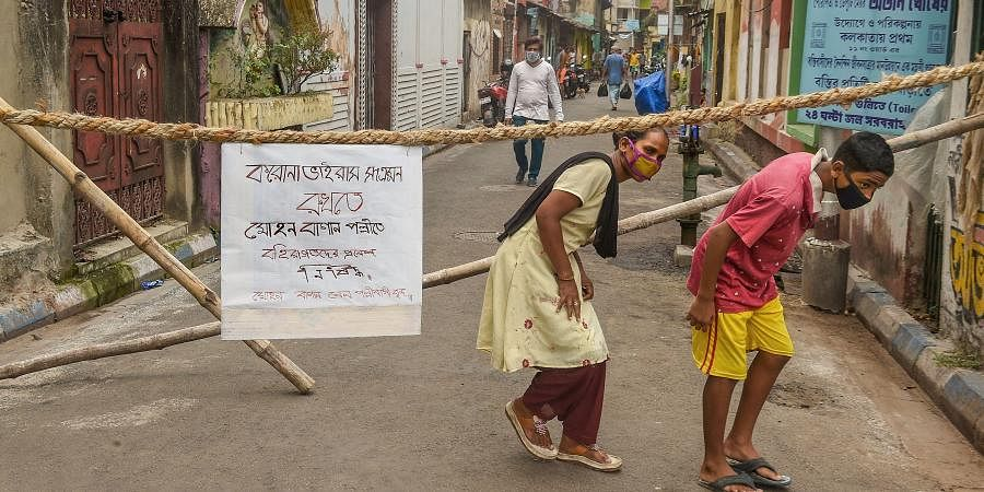 People cross barricades where a notice on 'no entry of outsiders' can be seen during a nationwide lockdown imposed in the wake of coronavirus pandemic in Kolkata