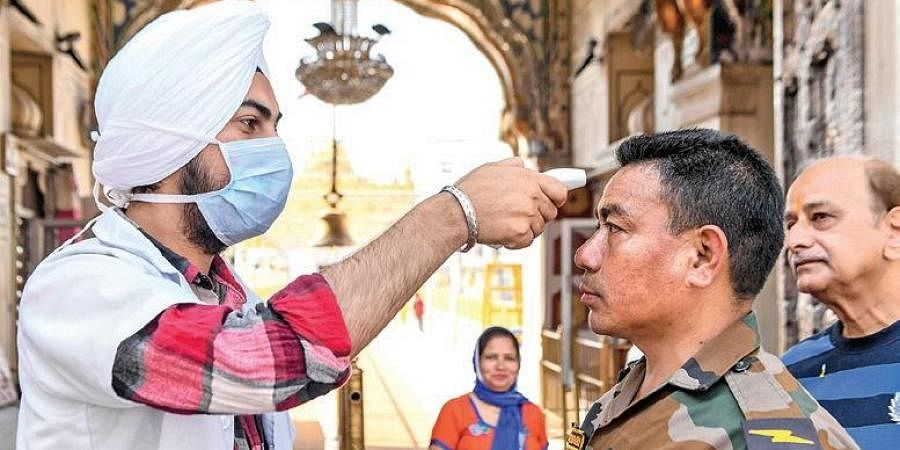 A health worker wearing a mask checks the body temperature of an army personnel.