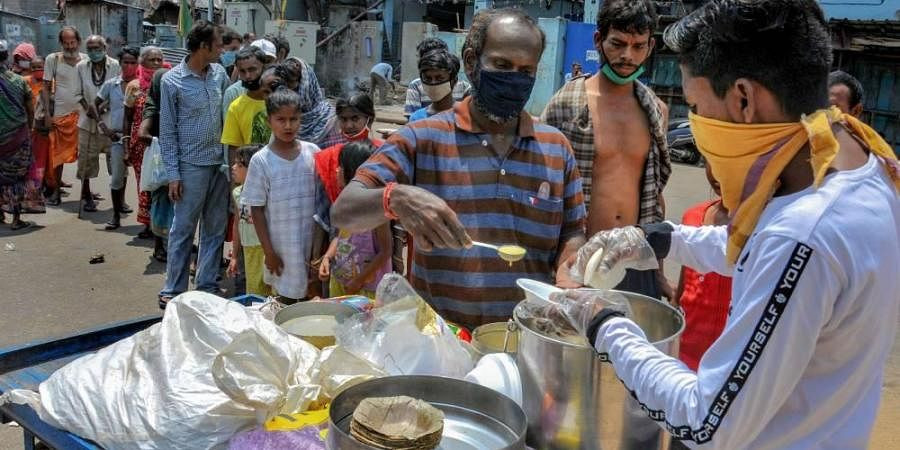 Volunteers distribute food to the needy and homeless people during the nationwide lockdown in the wake of coronavirus pandemic in Kolkata Thursday