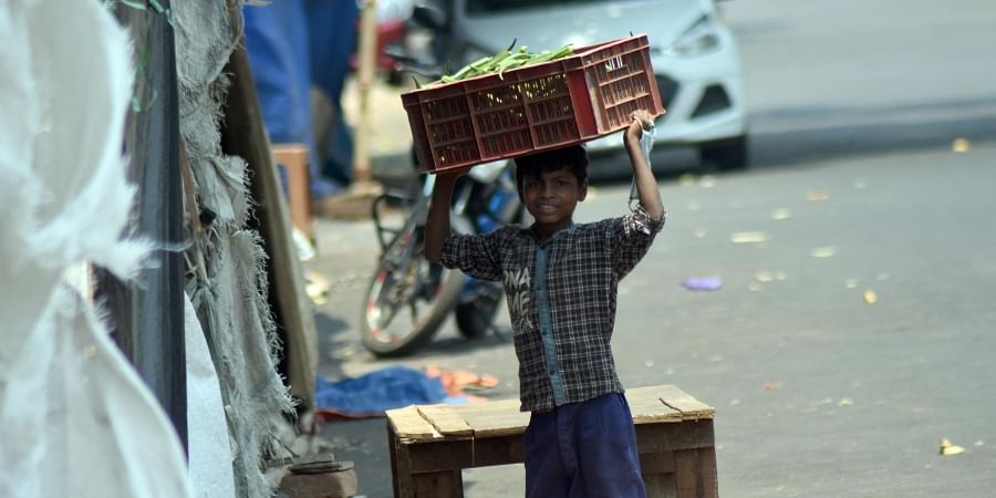 A boy carrying a box of vegetable for sell as helping his parent during lockdown in Bhubaneswar.