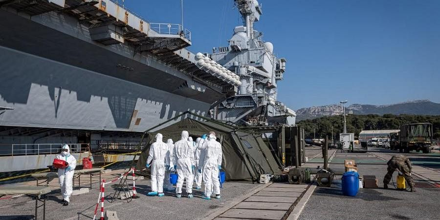 Team led by navy soldiers, firefighters and members of a Navy's disinfection special unit, disinfecting materials near the French aircraft carrier Charles de Gaulle. (Photo  AFP)