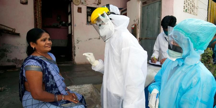Medical officials wear protective gear interacts with local residents during going for the door to door to check for new COVID-19 cases in Ahmedabad