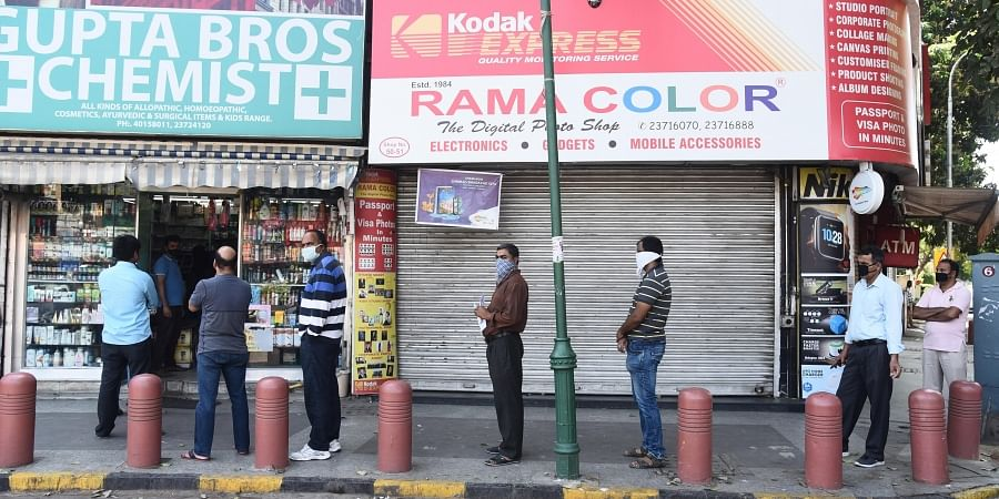 People stand in a queue outside a chemist shop while maintaining social distancing during a nationwide lockdown in the wake of coronavirus pandemic in New Delhi.