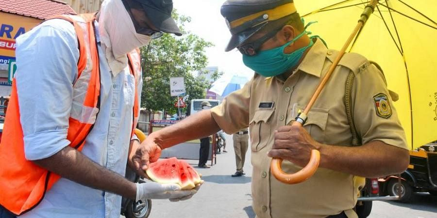 A volunteer provides watermelon to a cop on Covid-19 lockdown duty under the scorching sun in Kozhikode.