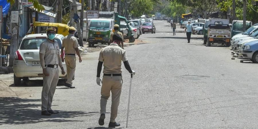 Security personnel stand guard on a deserted road at C block Jahangirpur area identified as COVID-19 hotspot during the nationwide lockdown to curb the spread of coronavirus in New Delhi Sunday