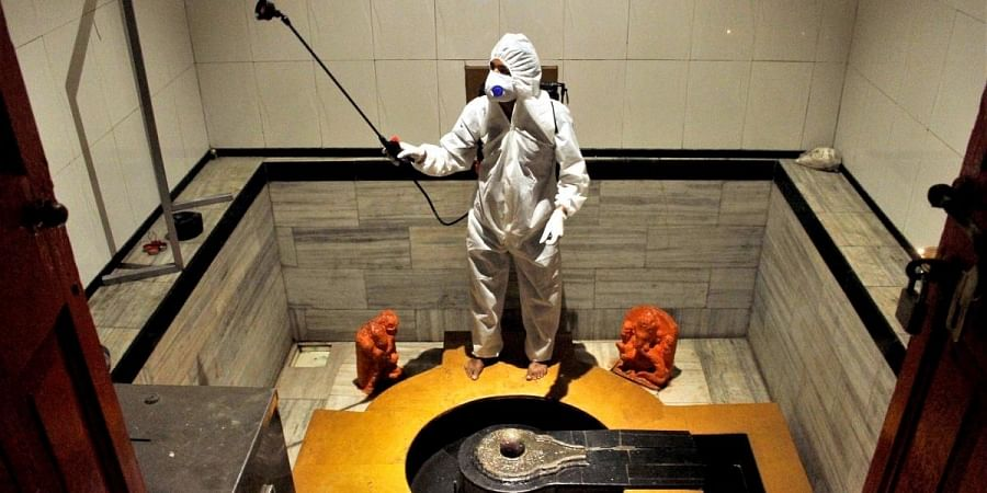 A worker wearing a protective suit disinfects a temple as a preventive measure against the spread of coronavirus disease, in Mumbai