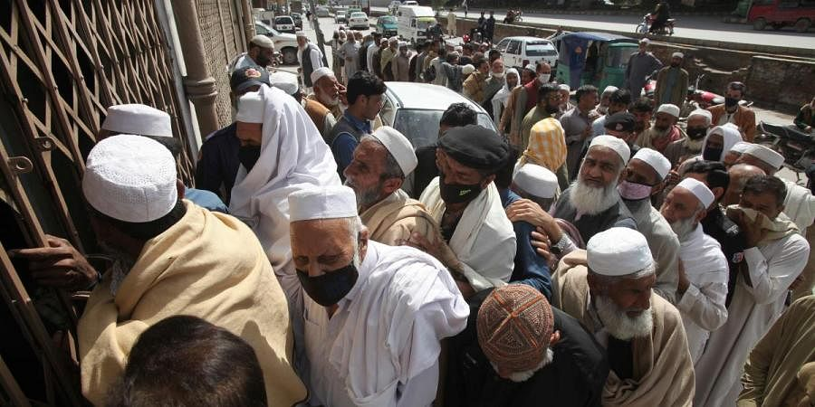 Pakistani government employees crowd together waiting to receive their salaries ignoring social distancing recommendations to help avoid the spread of coronavirus, outside a bank in Peshawar