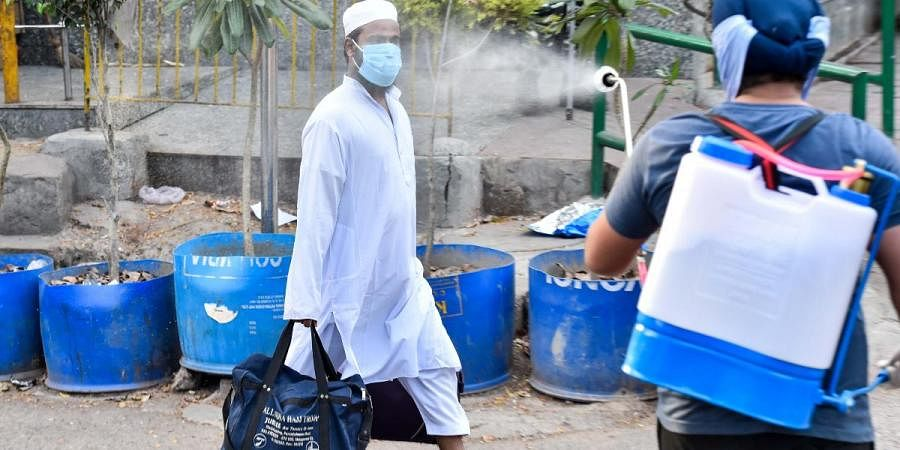 A volunteer sprays disinfectant on a masked man as he leaves the Nizamuddin area, where several people showed symptoms of infection from coronavirus