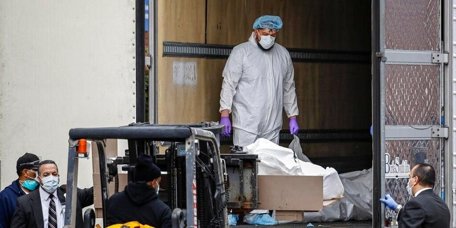 A body is loaded onto a refrigerated container truck used as a temporary morgue by medical workers at Brooklyn Hospital Center, New York.