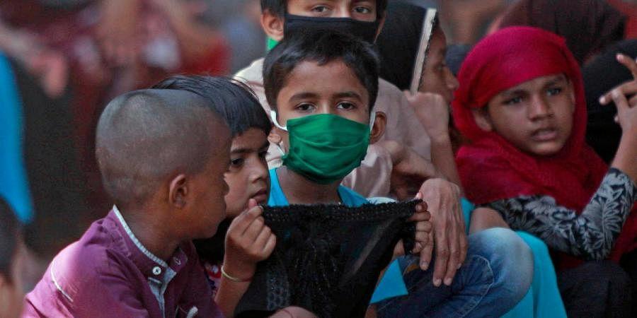 Children waiting for food packets during coronavirus lockdown, at Rafiq Nagar in Mumbai