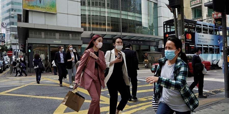 People wearing masks, walk across a street in Hong Kong, Monday, Feb. 24, 2020. The COVID-19 viral illness has sickened thousands of people throughout China and other countries since December.