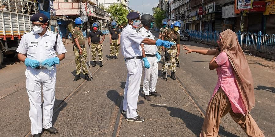 Security personnel stop a woman while patrolling at Mechua during a nationwide lockdown imposed in the wake of coronavirus pandemic in Kolkata.