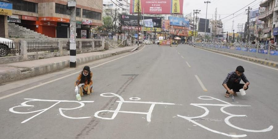 Youths writing slogans on deserted road in patna in support of lockdown. (Photo| Ranjit K Dey)