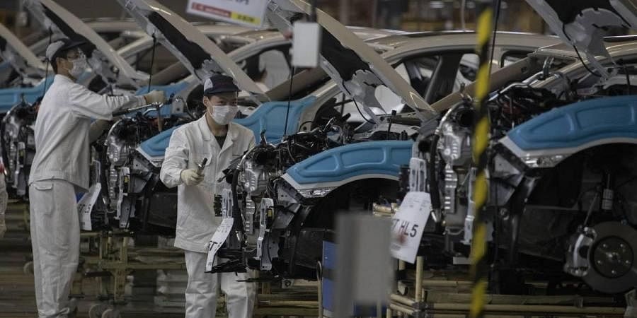 In this April 8, 2020, photo, employees work on a car assembly line at the Dongfeng Honda Automobile Co., Ltd factory in Wuhan in central China's Hubei province. Chinese leaders have reopened factories and shops in an effort to revive the economy, but the consumers whose spending propels most of China's growth have been slow to return to shopping malls and auto dealerships.