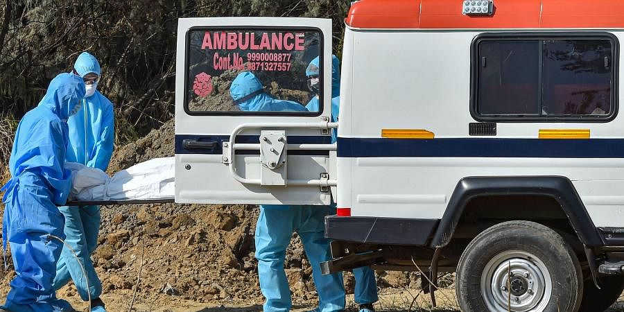 edics and family members arrive to perform burial of a person who died of COVID-19. (Photo  PTI)