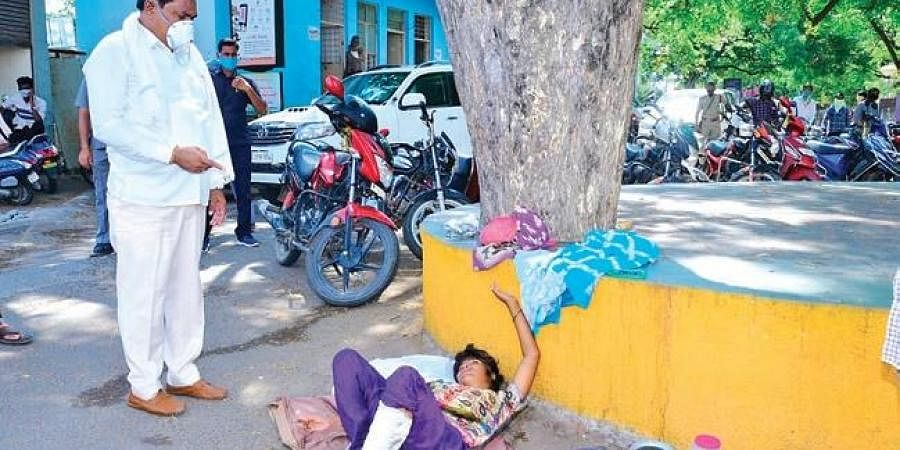 Panchayat Raj Minister Errabelli Dayakar Rao offers help to an injured woman staying outside MGM Hospital in Warangal on Tuesday