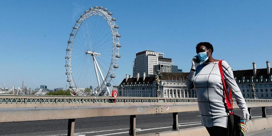 A woman wearing a protection mask to protect against coronavirus walks over Westminster Bridge in London